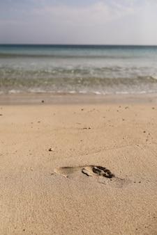 砂の上の男の素足の跡。