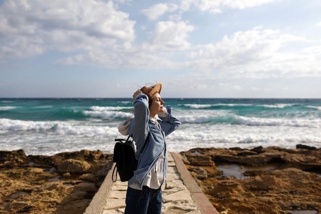 海の景色を眺める女性旅行者。キプロスの観光。海の背景に観光。女の子はビーチを旅します。熱帯のビーチ、夏休み、幸せ、楽しい、若い美しい流行に敏感な女性