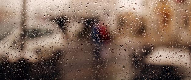ウィンドウに雨のしずくバナー。雨の水滴がガラスを流れ落ちます。雨、しずく、雨、水滴。