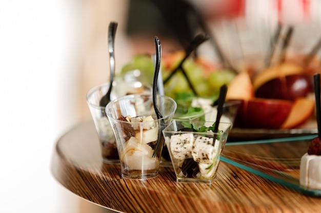 ケータリング。パーティー、企業パーティー、会議、フォーラム、宴会用の食品。ラズベリー、オリーブと異なる種類の高価なチーズ。セレクティブフォーカス