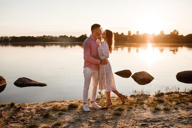 愛するカップルが夕暮れ時に湖でキスします。明るい光の光線で日没で湖の岸を歩いて恋に美しい若いカップル。コピースペース
