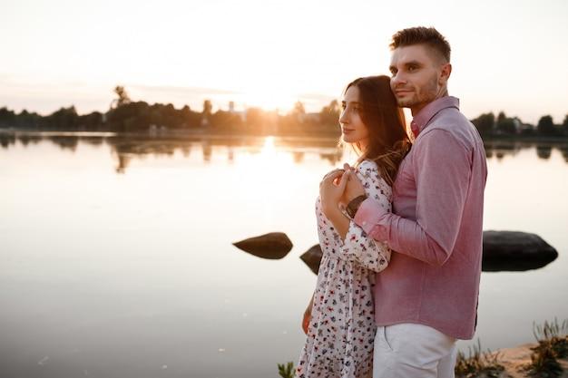 夕暮れ時の湖の上を抱いて愛するカップル。明るい光の光線で日没で湖の岸を歩いて恋に美しい若いカップル。コピースペース