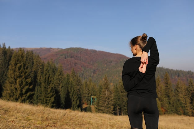 山で自然にストレッチ体操を行う若い女性。レギンスでヨガのポーズを練習するスポーツ少女。美しい森の風景