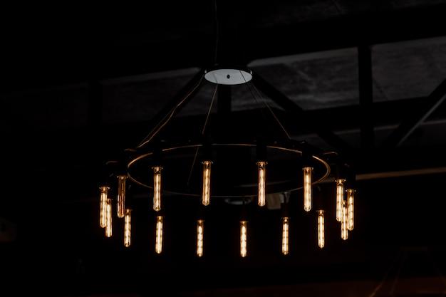 Старинный свет лампы интерьер в кафе или гостиной. лофт и деревенский стиль дома интерьеров. красивое винтажное роскошное светлое оформление смертной казни через повешение лампы накаляя в темноте.