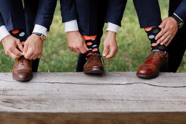 男性はスタイリッシュな靴下を履いています。スタイリッシュなスーツケース、男性の足、色とりどりの靴下、新しい靴。スタイル、ファッション、美容、休暇の概念。靴ひもを結ぶ。