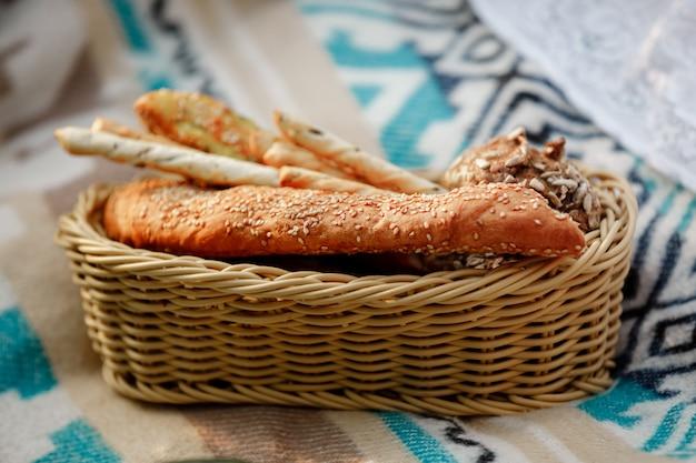 パンと籐のバスケット。バスケット内のパン、パン、グリッシーニ。ピクニックに新鮮なベーカリー製品。セレクティブフォーカス