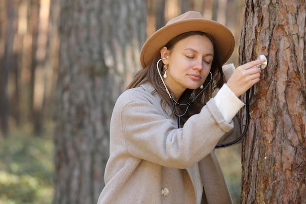 Стильная женщина в шляпе слушает дерево с помощью стетоскопа в лесу, концепция любви к окружающей среде