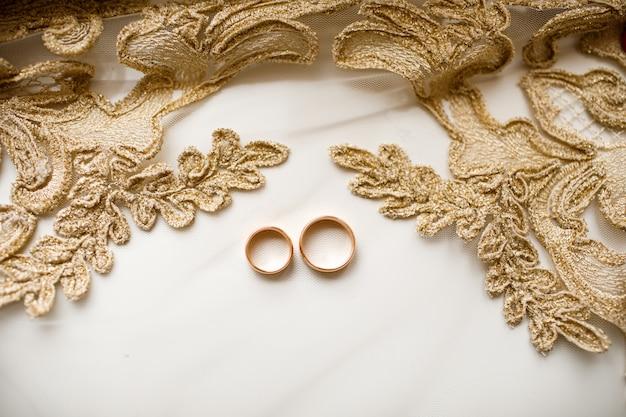 Пара золотых обручальных колец над вуалью с кружевом. свадебные аксессуары. выборочный фокус