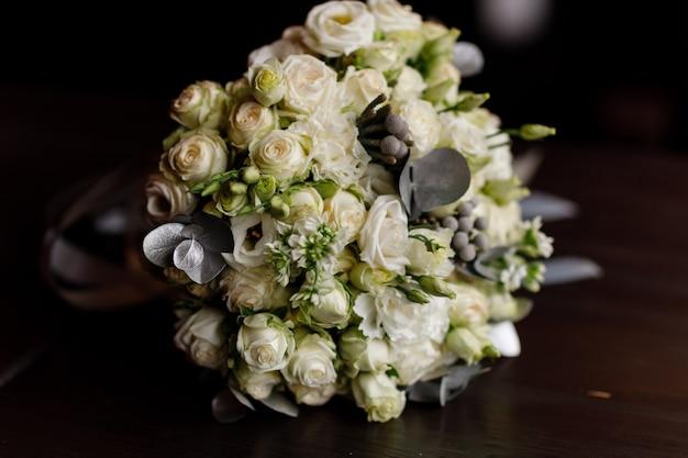 Свадебный букет. красивая из смешанных цветов и зелени, украшенная шелковой лентой, лежит на деревянном столе.
