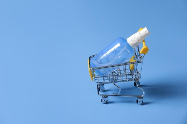 青色の背景に分離された明確なポンプボトルで明確な手の消毒剤。手の消毒剤は、細菌、細菌、ウイルスを殺すために使用されます