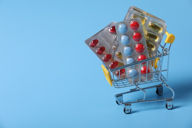 薬でいっぱいのショッピングカート。青色背景