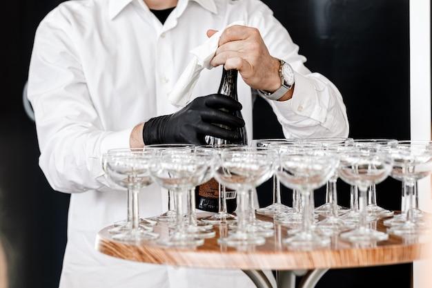 Официант в черных перчатках наливает шампанское в бокалы на деревянный стол