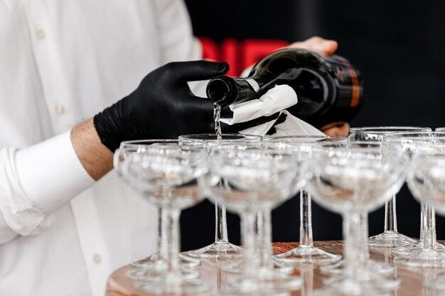 Официант в черных перчатках наливает шампанское в бокалы