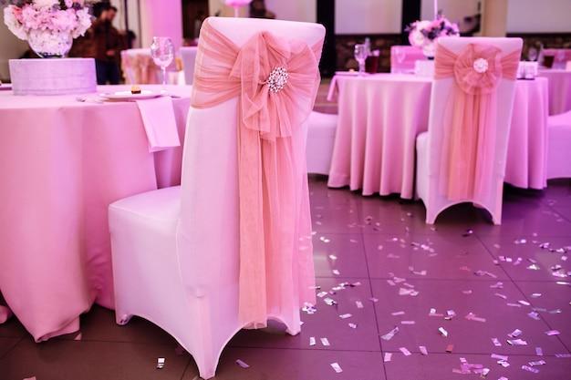Стулья с бантами и украшениями в ресторане в день свадьбы