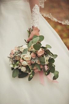 ピンクのバラ、白いカーネーションと緑の花のスタイリッシュなウェディングブーケ花嫁