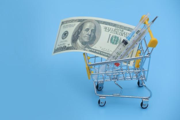 ドル紙幣ロールとショッピングカートの温度計