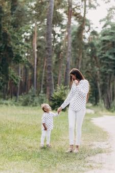 屋外の女の赤ちゃんを持つ母親。夏の散歩に幸せな家族母と娘が公園を散歩して、美しい夏の自然を楽しんでいます。セレクティブフォーカス