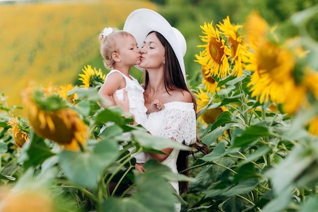 ひまわり畑で娘と帽子で幸せな母。ママとベビーの女の子が屋外で楽しんで。家族の概念。ママは娘にキスします。セレクティブフォーカス