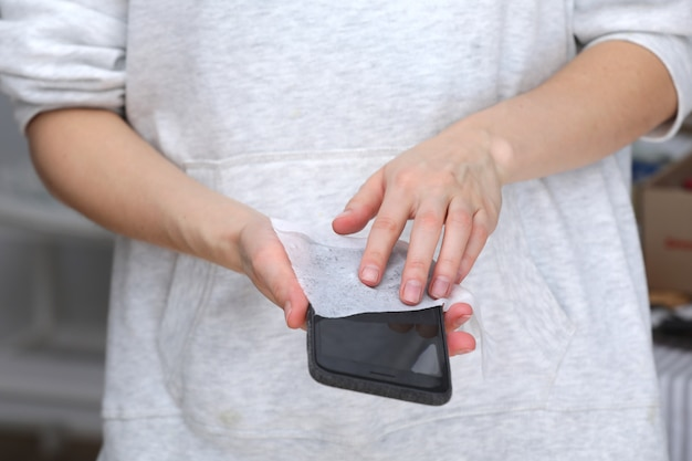 ウイルスからの携帯電話の消毒。電話スクリーン消毒ワイプ女性は抗菌ウェットティッシュで細菌を除去