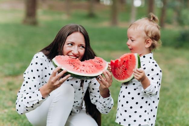 幸せな母と娘は夏の公園でスイカを食べる。公園でスイカを食べて幸せな笑顔の家族。母と娘は一緒に時間を過ごします。ダイエット、ビタミン、健康食品のコンセプト。セレクティブフォーカス
