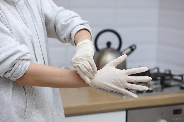 自宅やオフィスでの作業中に手に保護手袋を着用する若い女性は、検疫での蔓延中にウイルスが拡散するのを防ぐために、日中はテーブルラップトップで作業します。セレクティブフォーカス