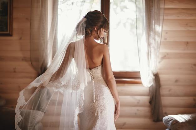 Красивая невеста в платье отвернулась от камеры. красивая невеста с вуалью моды. нежная невеста в свадебном платье.