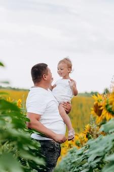 ひまわり畑で屋外の女の赤ちゃんを持つお父さんが大好きです。絆、家族、新しい人生。暖かい夏の日。家族の概念。セレクティブフォーカス