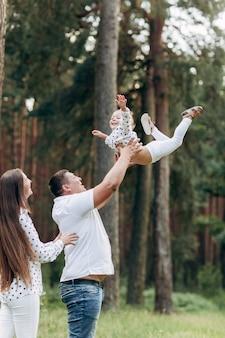 父は夏の休暇中に自然に娘を投げて回転させます。ママ、パパ、夏の時間に公園で遊んでいる女の子。飛んでいる女の子。フレンドリーな家族の概念。セレクティブフォーカス。