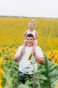 ひまわり畑でパパが赤ん坊の娘を肩に乗せています。夏休みのコンセプトです。父の日、赤ちゃんの日。一緒に時間を過ごす。家族の一見。
