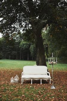 写真撮影のための結婚式の装飾。自然の中で古典的な白いソファ。インテリアのローソク足