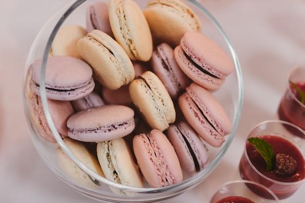 カラフルなマカロンは、キャンディーバーの一部として、丸みを帯びた透明な重量で飾られています