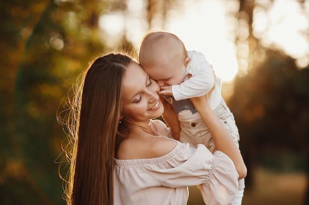 幸せな子供と彼のお母さんは、フィールドで屋外で楽しんでいます。ママは子供を抱きしめ、子供は抱擁し、母親にキスします。母の日。セレクティブフォーカス