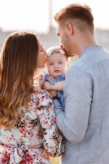お父さんとお母さんが自然で屋外の小さな娘にキスします。夏休みのコンセプトです。母の日、父の日、赤ちゃんの日。自然に一緒に時間を過ごす家族。家族の一見。セレクティブフォーカス