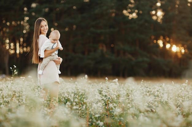 幸せな子供と彼のお母さんは、フィールドで屋外で楽しんでいます。ママは子供を抱きしめ、抱擁します。母の日。セレクティブフォーカス