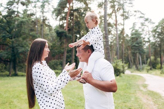 公園の森で赤ちゃんの娘を肩に乗せているパパ。夏休みのコンセプトです。父の日、母の日、赤ちゃんの日。一緒に時間を過ごす。家族の一見。セレクティブフォーカス