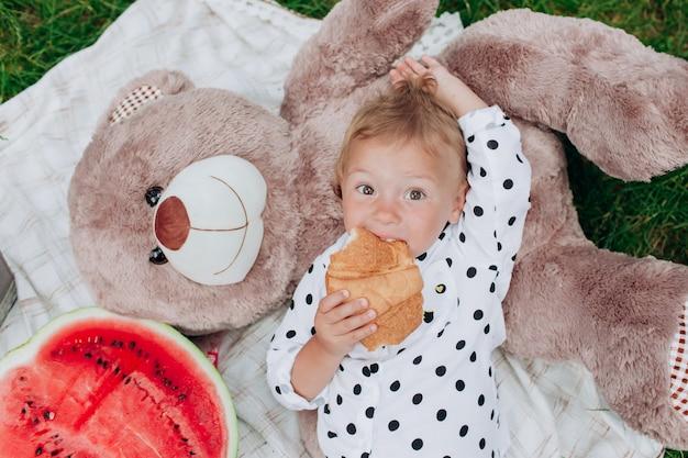かわいい女の子はピクニックの毛布の上に横たわるクロワッサンを食べています。幸せな夏の休日。幼年期と優しさの概念