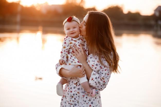 夕日に湖の近くの彼女の小さな娘にキスのママ。夏休みのコンセプトです。母の日、赤ちゃんの日。自然に一緒に時間を過ごす家族。家族の一見。セレクティブフォーカス