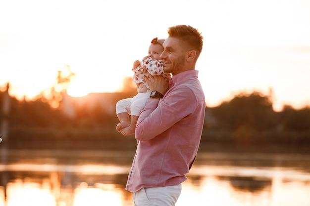お父さんが夕日に湖の近くの彼の小さな娘を抱き締めます。夏休みのコンセプトです。父の日、赤ちゃんの日。自然に一緒に時間を過ごす家族。家族の一見。セレクティブフォーカス