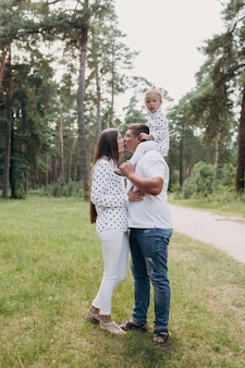 公園の森で赤ちゃんの娘を肩に乗せているパパ。夏休みのコンセプトです。父の日、母の日、赤ちゃんの日。一緒に時間を過ごす。家族の一見。カップルがキスします。