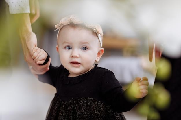 母、父は手をつないで娘は家で一緒に時間を楽しみます。足を下に見ます。母の日、父の日、赤ちゃんの日。若い家族の休日のコンセプトと愛のケアと次世代へのサポート。