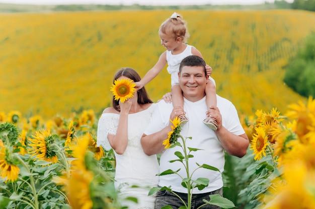 パパは花畑で赤ん坊の娘を肩に乗せています。夏休みのコンセプトです。父の日、母の日、赤ちゃんの日。一緒に時間を過ごす。家族の一見。セレクティブフォーカス