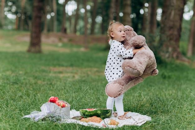 晴れた日に夏の公園で楽しんでいる大きなテディベアと愛らしい小さな幼児の女の子。夏の休日のピクニックのコンセプトです。セレクティブフォーカス。