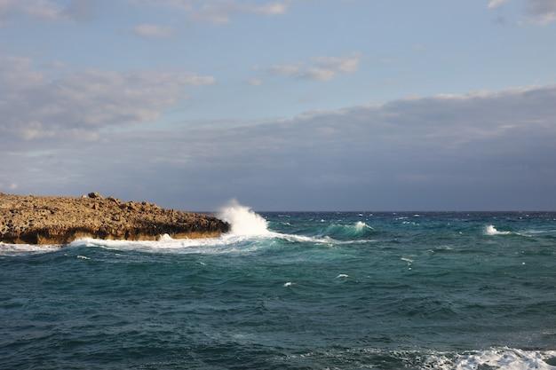 Волны, падающие на скалистые утесы на пляже, расположенном на кипре, такая погода может быть опасной для водных видов спорта, но одновременно волны и их брызги красивы и дики
