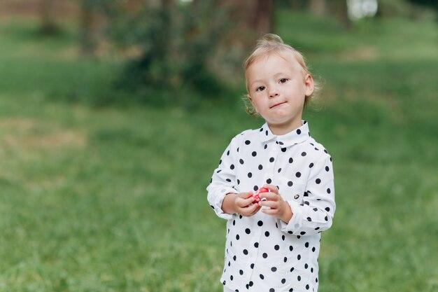 夏の日の公園の芝生の背景にかわいい女の子。幸せな夏の休日。セレクティブフォーカス