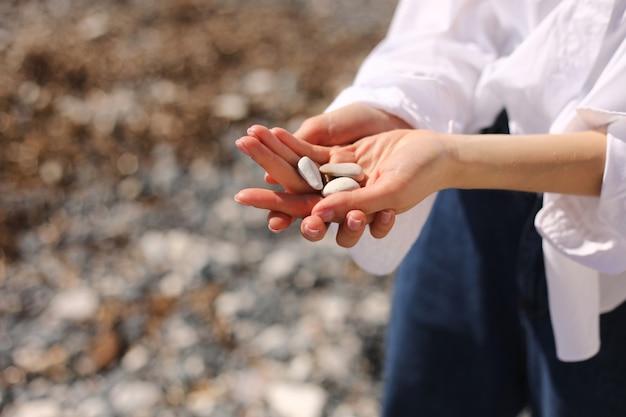 女性の手は、手のひら、海岸線、ビーチで小石を保持しています。セレクティブフォーカス
