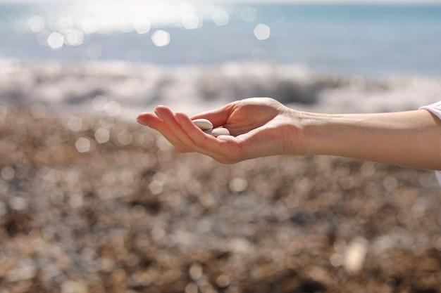 ビーチで青い海の近くの小さな小石を手に持って、石のビーチ、丸い形の小石、夏休みのお土産、ビーチの日、セレクティブフォーカスで小石を拾う女性の手