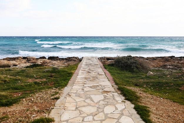 手前には小石と石のビーチを横切るコンクリートの通路。セレクティブフォーカス。