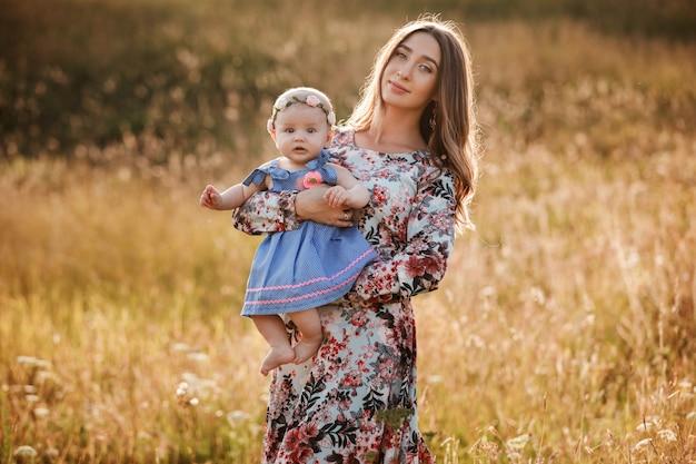 晴れた日に屋外の手で彼女のかわいい赤ちゃんの娘を持つ美しい母の肖像画。母の日、赤ちゃんの日。家族の夏の休日の概念。セレクティブフォーカス
