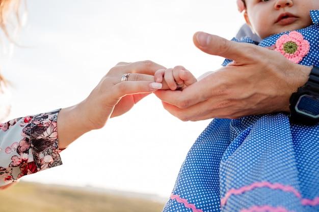 子供の手を母と父の手に。夏休みのコンセプトです。母の日、父の日、赤ちゃんの日。自然に一緒に時間を過ごす家族。家族の一見。セレクティブフォーカス