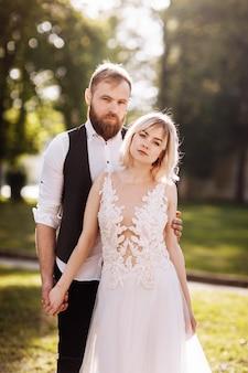 シンプルなウェディングドレスで幸せな結婚されていたカップル。結婚式のカップル。スタイリッシュな新婚カップル。花嫁のスタイリッシュな白いドレス。結婚の概念。